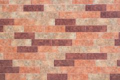 The texture of a brick wall of decorative multicolored rectangular bricks with noise, scratches. And stains royalty free stock photos