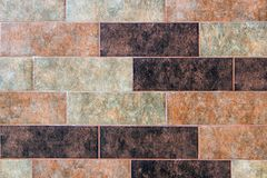 The texture of a brick wall of decorative multicolored rectangular bricks with noise, scratches. And stains royalty free stock photography