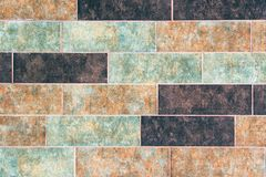 The texture of a brick wall of decorative multicolored rectangular bricks with noise, scratches royalty free stock photography