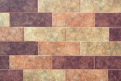 The texture of a brick wall of decorative multicolored rectangular bricks with noise, scratches. And stains stock photo