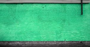 The texture of the brick wall of many rows of bricks painted in green colo. R royalty free stock photo