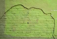 Texture brick wall with remains of plaster, painted with green p Stock Photo