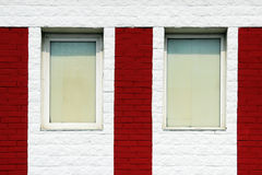 texture of bright red brick wall with white stripes and windows on a sunny day. Stock Image