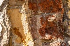 Broken uneven brick wall. The texture of the broken uneven brick wall stock image