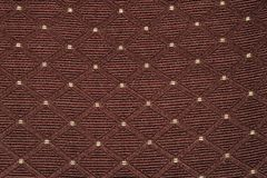Texture of brown fabric with rombic pattern with white dot. Texture of brown fabric with diamond or rombic pattern with white dot royalty free stock photos