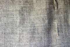 Texture of brown old canvas, linen natural material with a coarse perpendicular interlacing of the fibers of the fabric. The background stock image
