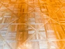 Texture of brown textured yellow wooden floor, parquet of small rectangular plates, lacquered wood plank boards. The background royalty free stock photos