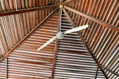 The texture of a brown wooden roof is abstract of the beams of logs arranged vertically horizontally and a large ceiling fan stock photos
