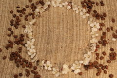 Texture of burlap with scattered white flowers and coffee beans. Texture of coarse cloth with scattered white flowers and coffee beans stock images