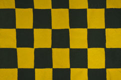 Texture of a chessboard. Texture with a chessboard pattern. Background is made of sewn pieces of yellow fabric and black fabric Royalty Free Stock Images