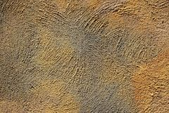 Texture of coarse plaster of yellow and gray colors on the wall Stock Image