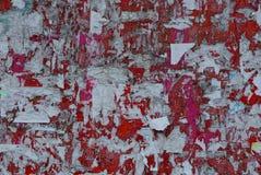 Texture colorée des annonces de papier déchirées sur un conseil rouge image libre de droits