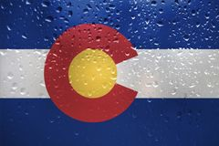 The texture of the Colorado flag on the glass with drops of rain vector illustration