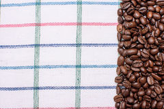 Texture of a colored towel, a towel of a cellular type, on which lies a certain amount of brown coffee beans. Top view with a bunc Stock Photography