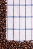 Texture of a colored towel, a towel of a cellular type, on which lies a certain amount of brown coffee beans. Top view with a bunc Royalty Free Stock Photos