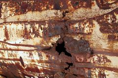 A texture of a corrosion pitting of rusty metal and a hole. Brown and licht yellow colors and texture of corrosion of rusty metal. A hole stock image