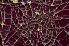 The texture of the cracked paint burgundy color with yellow streaks.  royalty free stock photo
