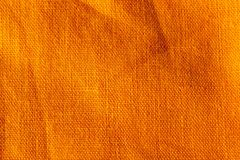 The texture of crumpled cotton linen carrot orange red color fabric texture background. The texture of a crumpled cotton linen carrot orange red color r fabric royalty free stock image