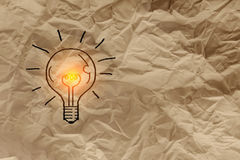 Texture of crumpled paper. Crumpled fold brown paper sheet background WITH LIGHT BULB DRAWING stock image