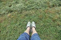 Texture d'herbe avec l'homme dans des espadrilles Images stock