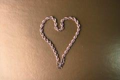 Texture d'un tissage unique de belle chaîne de fête d'or sous forme de coeur sur un espace de fond et de copie d'or jaune photographie stock libre de droits