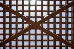 Texture d'un trellis abstrait en bois brun avec les cellules carrées avec des trous des panneaux des faisceaux de rondin disposés photo libre de droits