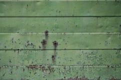 Texture d'un vieux mur vert en métal avec des dommages significatifs d'exposition aux conditions atmosphériques et aux dampnes dé Photographie stock libre de droits