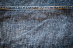 Texture of dark fabric blue jeans textile with seam. Stock Image