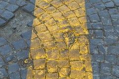 Texture of dark grey cobblestones with yellow line Stock Photo