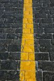 Texture of dark grey cobblestones with yellow stripe as road marking on Red square in Moscow. Closeup royalty free stock image