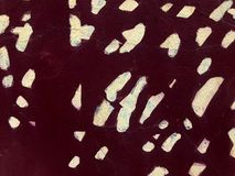 Texture of dark red maroon stone old cracked wall painted with paint with white spots, dots. The background stock photography
