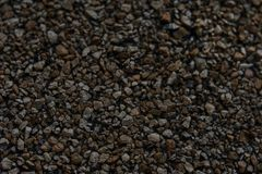 Texture of a Dark Roofing Shingle. Image shows a macro view, or close up view of a roofing shingle in darker colors. The greys, blacks and dark browns of the stock photo