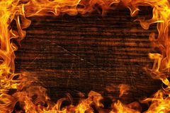 Texture of dark wood and frame out of the fire. Wood brown texture around the burning bright flame. Background of old panels. Copy space royalty free stock photography
