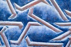 Texture de belles étoiles d'Arabe et lignes, rayures et modèles convexes bruns sur un vieux tissu en caoutchouc porté bleu Photographie stock