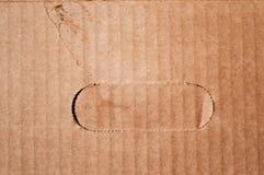 Texture de boîte en carton brune endommagée propre avec la poignée cutted Photographie stock