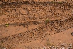Texture de boue brune humide avec l'empreinte de pas de voies et de chaussure de pneu de voiture Image libre de droits