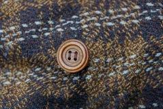 Texture de Brown d'un morceau d'habillement avec un bouton Photos stock