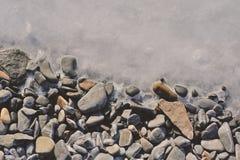 Texture de glace et de caillou glacé sur la plage Photo libre de droits