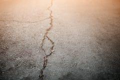 Texture de la vieille route avec des fissures Surface d'asphalte sur la rue Éclat de lumière Image stock
