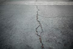 Texture de la vieille route avec des fissures Surface d'asphalte sur la rue Image stock