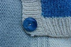 Texture de laine de gris bleu d'un chandail avec un bouton Photographie stock