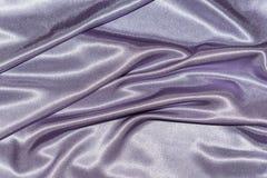 Texture de luxe en soie de tissu de tissu de beau satin pourpre onduleux élégant lisse de violette, conception abstraite de fond  photos stock