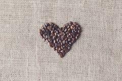 Texture de toile de jute avec la forme de coeur de grains de café Images stock