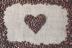 Texture de toile de jute avec la forme de coeur de grains de café Image stock