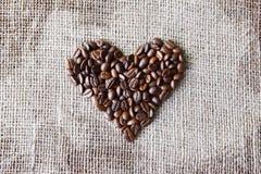 Texture de toile de jute avec la forme de coeur de grains de café Photographie stock