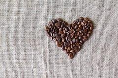 Texture de toile de jute avec la forme de coeur de grains de café Image libre de droits