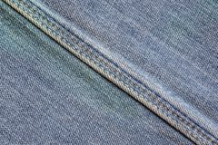 Denim fabric with seam. Texture of denim with a diagonal sewn seam. Fabric blue with embroidery. Stylish background of shabby denim. Jeans with a seam Royalty Free Stock Photography