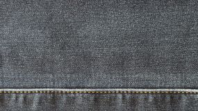 Texture of the surface of denim material. The texture of the denim fabric is gray, with a horizontal seam Stock Images
