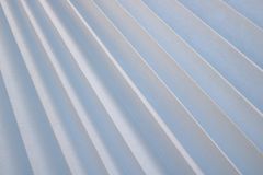 Texture of diagonal stripes with a shadow, with triangular curved ribs, edges of light white fabric, paper with triangular strips stock images