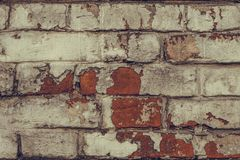 Texture of dilapidated brick wall close up. Dirty shabby brick wall in white peeling paint. White brick wall texture background. G stock image